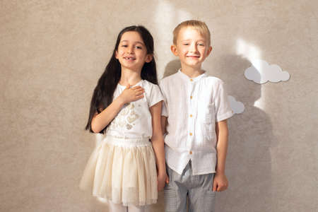 Portrait of a boy and a girl child laughing and holding hands against a wall background with clouds and sunlight. Friends are children's emotions. Toothless smiles.