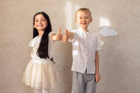 Portrait of a boy and a girl child laughing show thumbs up, gesture class, against the background of a wall with clouds and sunlight. Friends are children's emotions. Toothless smiles.