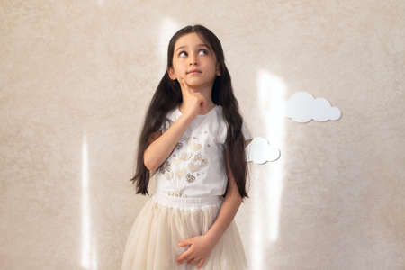 Portrait of a girl child musing on the background of a wall with clouds and sunlight. Children's emotions.