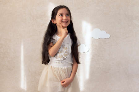 Portrait of a baby girl laughing against a wall background with clouds and sunlight. A smile without an upper tooth. Children's emotions. Standard-Bild