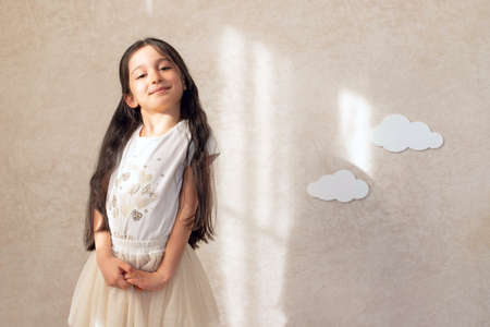Portrait of a baby girl smiling against a wall background with clouds and sunlight. Children's emotions.