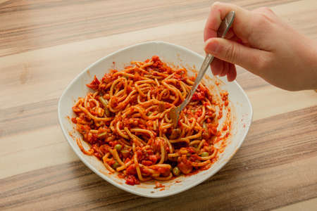Eating spaghetti bolognese whit the fork from a white plate