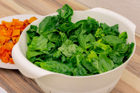 Fresh green and healthy lettuce put in a big white plastic colander