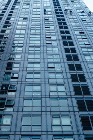 Group of Cleaners are cleaning windows of a office building