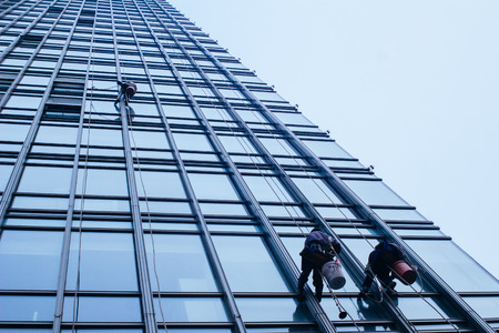 Group of Cleaners are cleaning windows of a office building photo