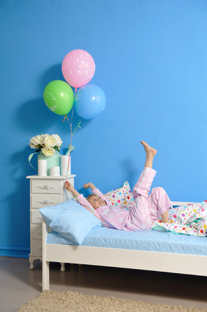 Beautiful baby girl sleeping in her bed and waking up Stock Photo