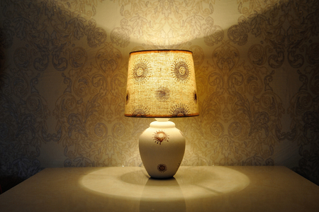 A small table lamp, with a yellow light on the bedside table Stock Photo - 84329851