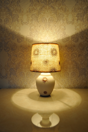 A small table lamp, with a yellow light on the bedside table Stock Photo - 84329890