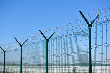 The barbed wire fence on blue sky background