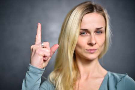 Girl shows up an index finger, expressing a sign of attention.