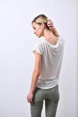 ブロンドの女の子の耳と髪を引いて首を示します。
