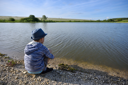 The boy is sitting by the river and wants to fish. Stock fotó