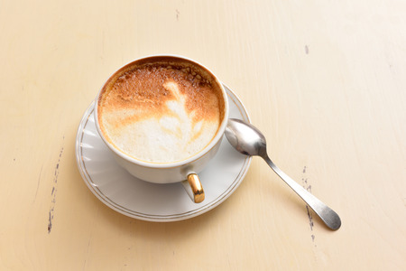 A cup of coffee and a spoon on a vintage table.
