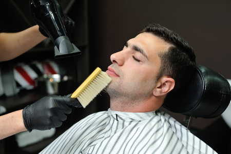 After shaving beard, hairdresser is removed hair from the face with a brush. Stock Photo