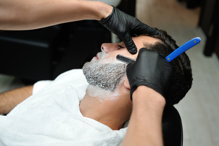 Hairdresser shaves mans beard with a blade in a male barber shop.