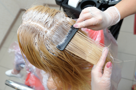The hairdresser smears the paint on his hair with a comb, for coloring the blonde..