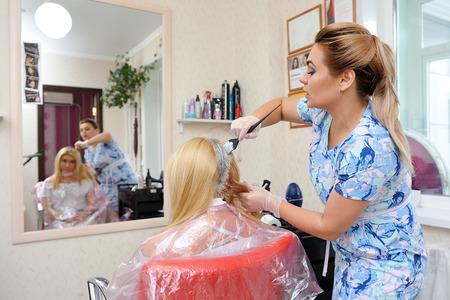 The hairdresser uses a brush to apply the dye to the hair, for dyeing.