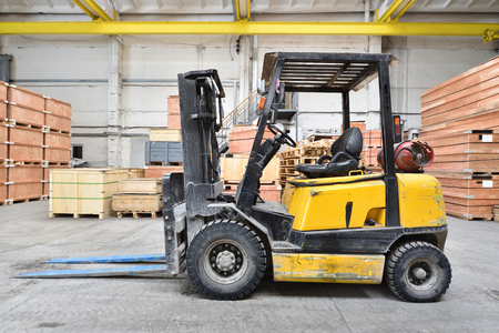 The forklift is old and scratched in a large and light warehouse. Yellow color. Foto de archivo