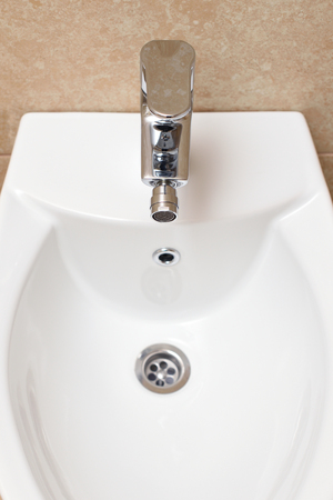 Bidet is white in the bathroom, new. Bidet - the device to wash. Stock Photo