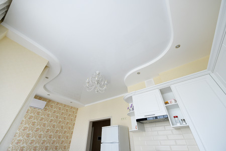 Stretch ceiling in the kitchen. Stretch ceiling white and complex shape.