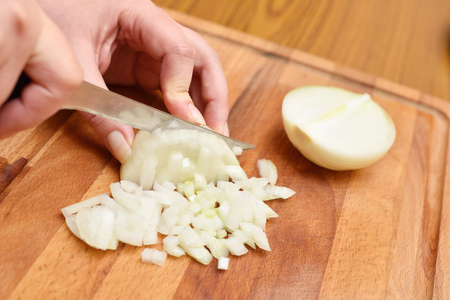 Female hands using a knife cut a fresh onion on a cutting board. Close-up.