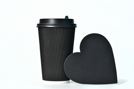 A disposable black paper cup for coffee and a heart-shaped sign. Paper cups for hot coffee. Coffee to go. Paper cup for coffee.