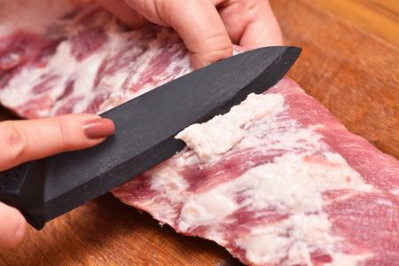 Enlevez l'excès de gras de la viande de porc sur les côtes. Pour éliminer les graisses indésirables sur la viande.