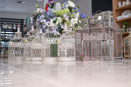 Cages for decorations, of various shapes, are on the floor in the store and sold
