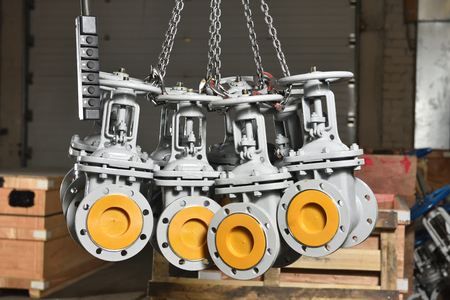 The new mechanical valves of gray color suspended on chains on the industrial elevator. Valves for water or gas suspended in chains at the factory.