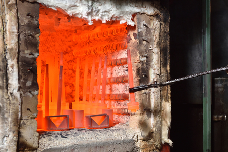 Worker pulls out the heated parts with tongs from an electric furnace for hardening metal. Work with high temperature in heavy industry in a valve manufacturing plant, close up 스톡 콘텐츠