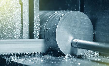 Il processo di taglio del metallo con una sega elettrica in una fabbrica. La sega elettrica taglia il metallo rotondo, primo piano