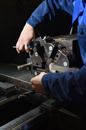 A worker in blue workwear performs maintenance on the CNC machine to install drills in the turret for working with metal. Hands of the worker close up