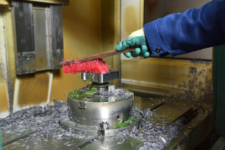Worker removes metal shavings with a brush after working on a CNC machine. Close-up