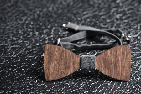 Stylish men's brown wooden bow tie with gray fabric on an iron rough surface. Accessory for brutal men, close up