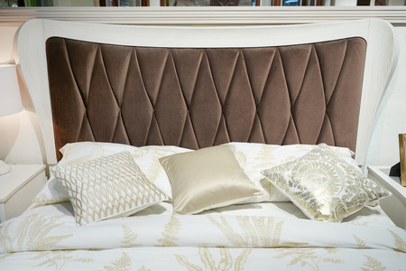 Bed with a big brown soft headboard and pillows.