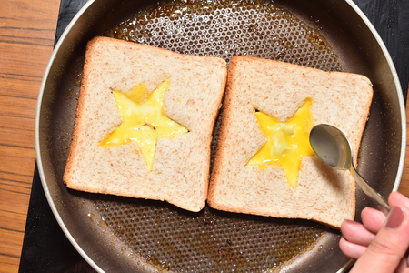 Roasting bread toasts with a star-shaped middle and a girl's hand fills it with a beaten egg to create a sandwich. Bread is fried for sandwiches in a pan with a non-stick coating Banco de Imagens