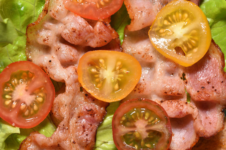 Fried bacon on lettuce and cherry tomatoes, for a tasty breakfast.
