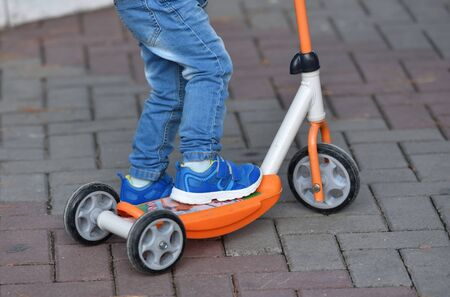 Boy child in blue jeans and sneakers riding a scooter. 스톡 콘텐츠