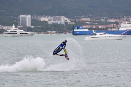 Gelendzhik, Russia - September 8, 2018: Young athlete guy doing flips on a jet ski in the sea. Close-up