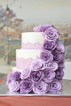 A beautiful three-tiered wedding cake decorated with mastic and roses fashioned from mastic of lilac color.