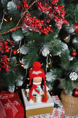 A cute children's soft doll in a red hat stands next to a Christmas tree. New Year's gift children's soft doll Archivio Fotografico