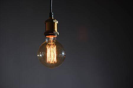 Schöne große runde Retro-Lampe mit Glühfäden auf dem Hintergrund einer grauen Wand Standard-Bild