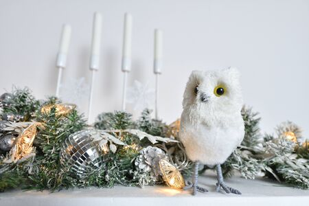A white owl figurine stands on a shelf with candles decorated for Christmas or New Year.