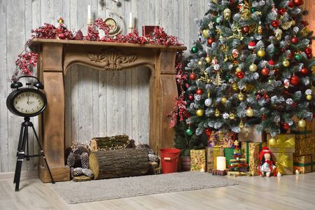 Christmas interior in brown tones with a Christmas tree, gifts, a wooden fireplace and a clock on a tripod