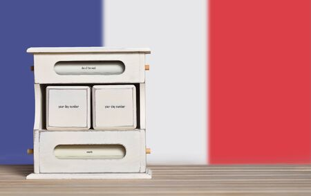 Wooden retro calendar with free space for a date on the background of the flag of France. Template for writing the dates of the national holidays of France with free text space.
