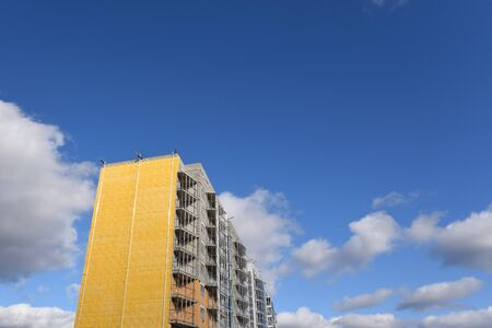 Construction of a residential building and insulation of its external wall with special heat-insulating material. Wall with thermal insulation against the blue sky