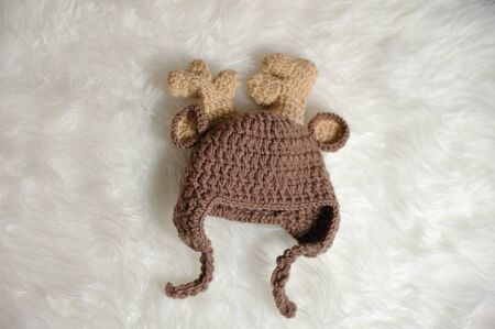 Cute children's knitted hat in the shape of a deer on a white carpet background