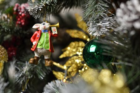 A decoration in the form of a bunny with a musical trumpet hanging on a Christmas tree
