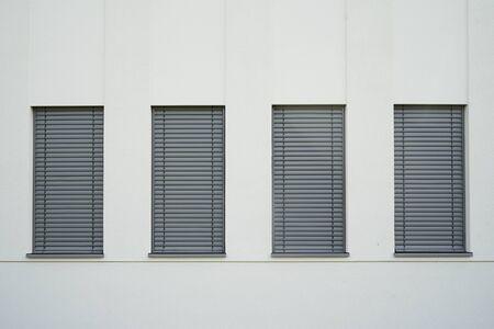 Four narrow windows with closed gray shutters on the light wall. 版權商用圖片