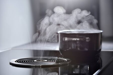 Electric induction cooker with built-in ventilation and extractor hood which draws steam from boiling water in a pan Stock Photo